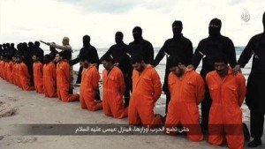 Still image from video shows men purported to be Egyptian Christians held captive by the Islamic State kneeling in front of armed men along a beach said to be near Tripoli